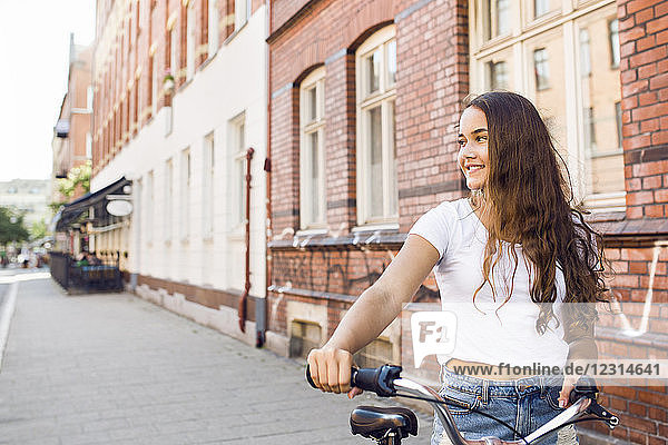 Portrait of teenage girl (14-15) with bicycle