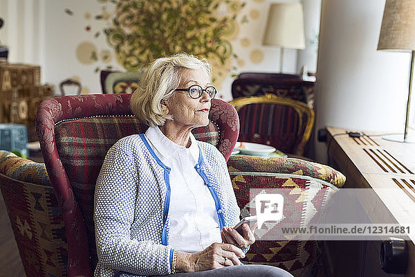 Senior woman looking through window during coffee break in cafe