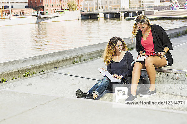 Two young women reading books by river