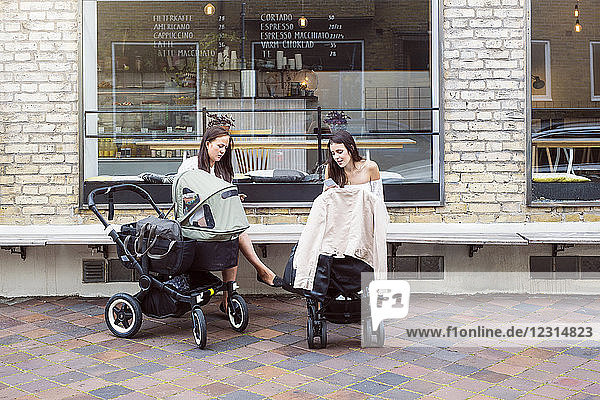 Two young mothers with baby strollers sitting in front of cafe