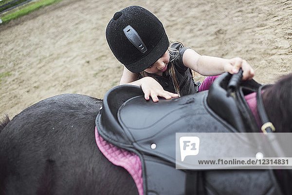 Girl (4-5) mounting pony Girl (4-5) mounting pony