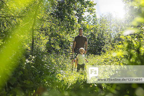 Father and son (2-3) in forest