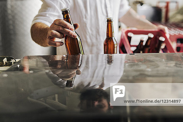 Mid section of brewery worker holding beer bottles