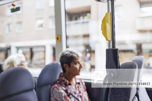 Woman sitting in bus and looking through window Woman sitting in bus and looking through window