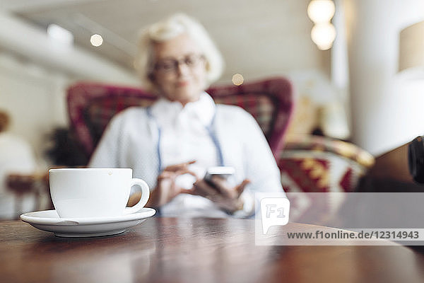 Coffee cup on table and senior woman using mobile phone during coffee break in cafe