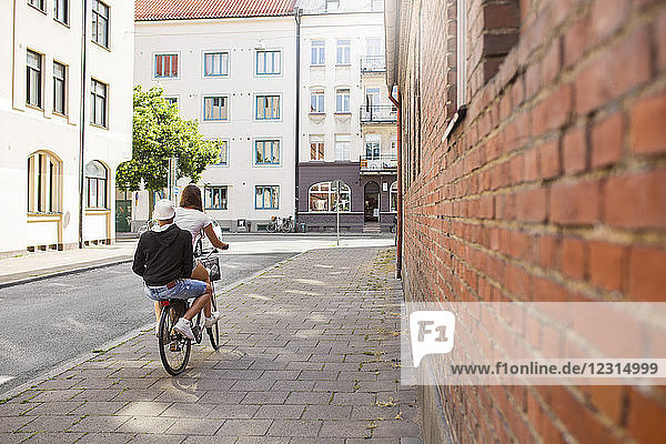 Teenage girl and teenage boy (14-15) riding bicycle together