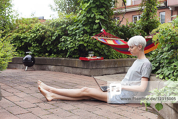 Woman sitting in garden and using laptop Woman sitting in garden and using laptop