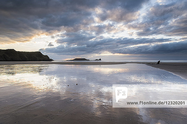 Sunset clouds reflected in wet sand  Rhossili Bay  Gower Peninsula  South Wales  United Kingdom  Europe