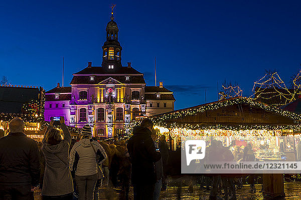 Christmas market at the main square of Luneburg with view to the town hall at dusk  Luneburg  Lower Saxony  Germany  Europe