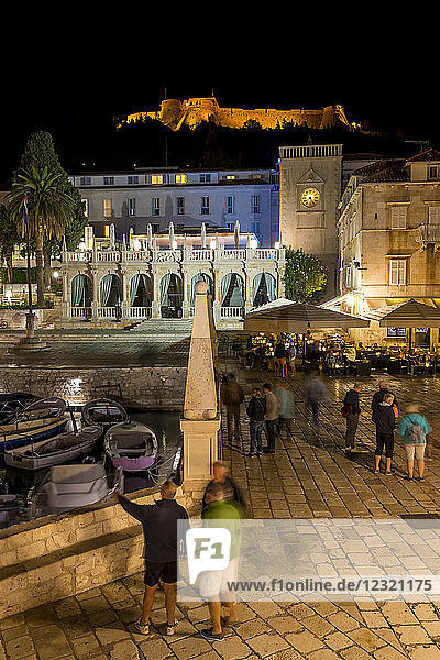 Night shot of the main square (Trg Svetog Stjepana) of Hvar Town with view to the Spanish Fortress in the background  Hvar  Croatia  Europe