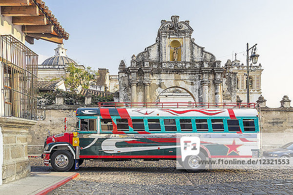 A typical colorful painted chicken bus passing at the entrance gate of San Francisco Church in Antigua  UNESCO World Heritage Site  Guatemala  Central America