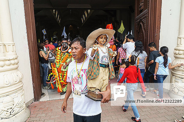 Worshipper at the door of the Cathedral with Baby Jesus statuette at the annual Ati-Atihan Festival  Kalibo Island  Philippines  Southeast Asia  Asia