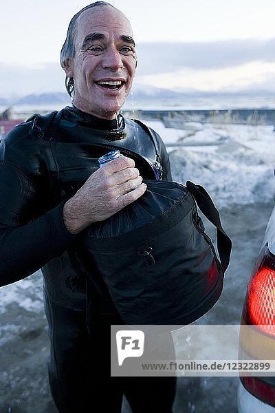 Man rinsing off after surfing in Kachemak Bay  South-central Alaska; Homer  Alaska  United States of America