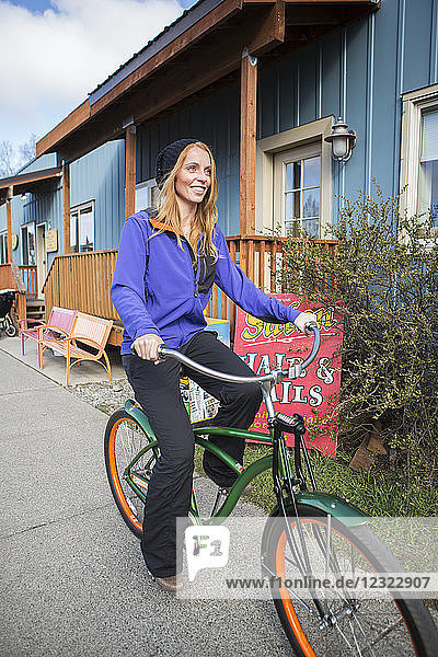 Young woman on a bicycle in downtown Anchorage  South-central Alaska; Anchorage  Alaska  United States of America