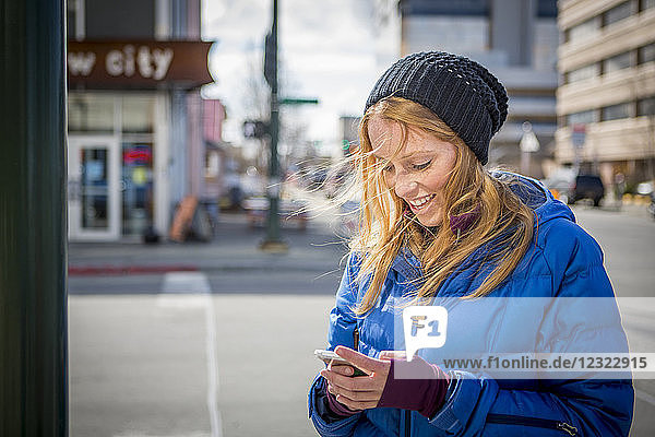 Young woman texting on her smartphone in downtown Anchorage  South-central Alaska; Anchorage  Alaska  United States of America