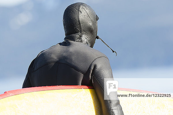 Close-up of a surfer wearing a wetsuit with hood and carrying his surfboard  Kenai Peninsula outer coast  South-central Alaska; Alaska  United States of America