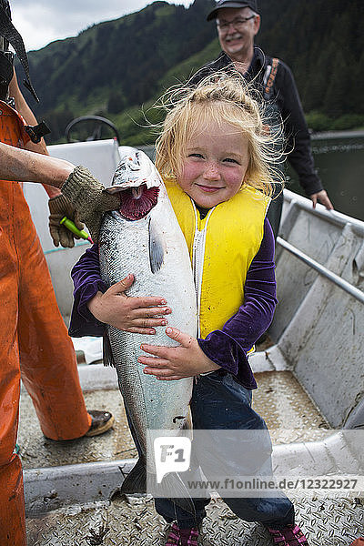 Young girl holding a salmon in a set-net skiff  South-central Alaska; Seldovia  Alaska  United States of America