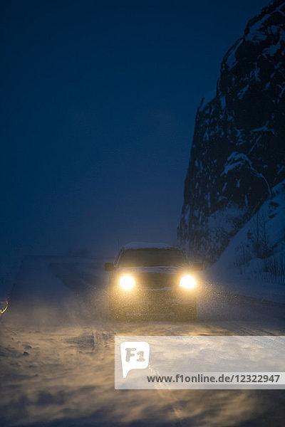 Car headlights illuminate the blowing snow on the Seward Highway during a dark winter night  Kenai Peninsula  South-central Alaska; Alaska  United States of America