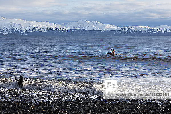 Sea kayaking in Kachemak Bay with a dog running in the water along the shore  South-central Alaska; Homer  Alaska  United States of America