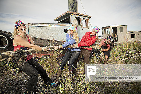 Group of friends playing tug with a large rope along coastal Homer,  South-central Alaska; Homer,  Alaska,  United States of America