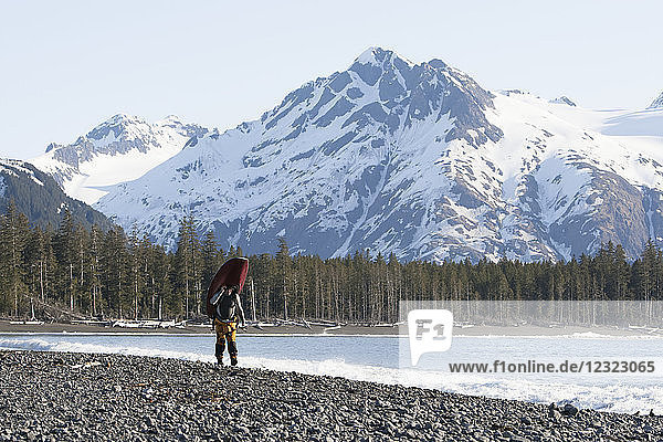 Man walking with a kayak  Kenai Peninsula Outer Coast  South-central Alaska; Alaska  United States of America