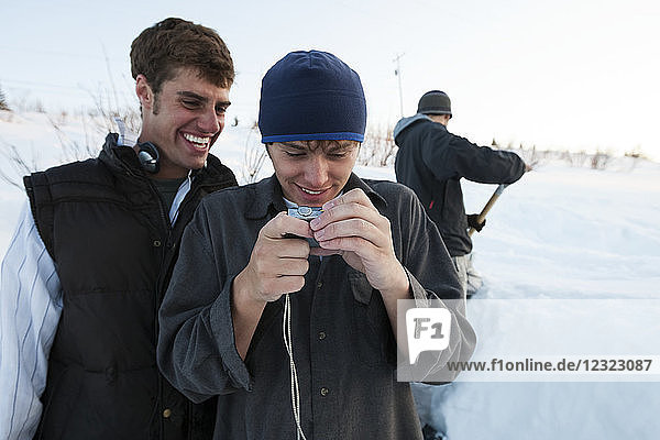 Snowboarders looking at pictures on a digital camera  South-central Alaska; Homer  Alaska  United States of America