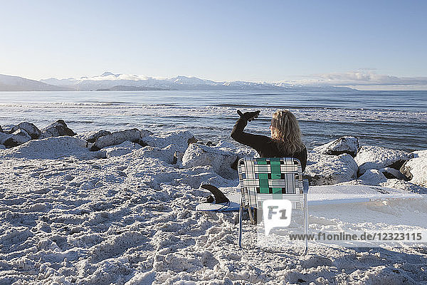 Female surfer relaxed in lawn chair on the snowy shore enjoying the view of Kachemak Bay  South-central Alaska; Homer  Alaska  United States of America