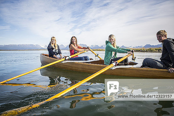 Young adults rowing in a canoe  South-central Alaska; Homer  Alaska  United States of America