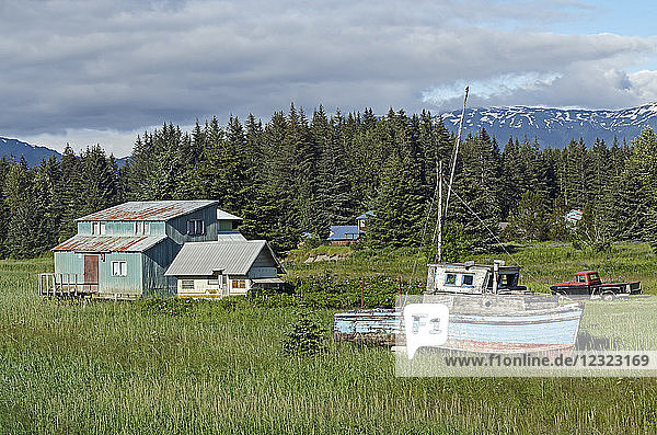 Rustic wooden boat and home on the grass shore near ferry dock  Southeast Alaska; Gustavus  Alaska  United States of America
