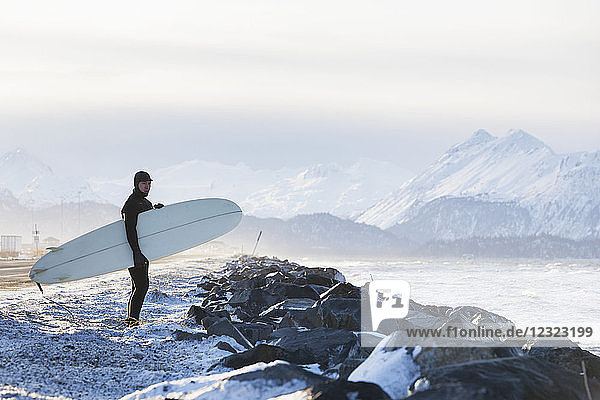 Surfer with surfboard looking out over Kachemak Bay  South-central Alaska; Homer  Alaska  United States of America