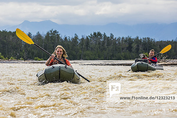 Young couple with their dog in pack rafts in Jarvis Creek  Interior Alaska; Alaska  United States of America