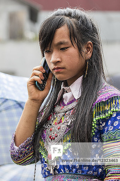 Hmong woman talking on a mobile phone at the Sunday market; Bac Ha  Lao Cai  Vietnam