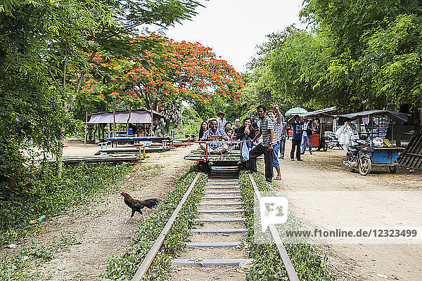 People sitting on a Norry  the bamboo train  at the Norry Railway Station; Battambang  Cambodia