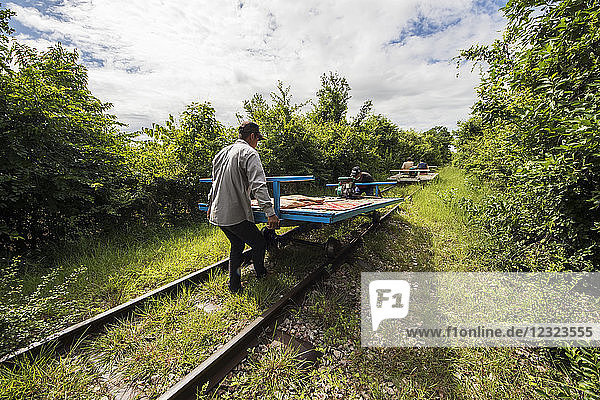Men placing the bamboo platform on the wheels of the Norry  the bamboo train; Battambang  Cambodia