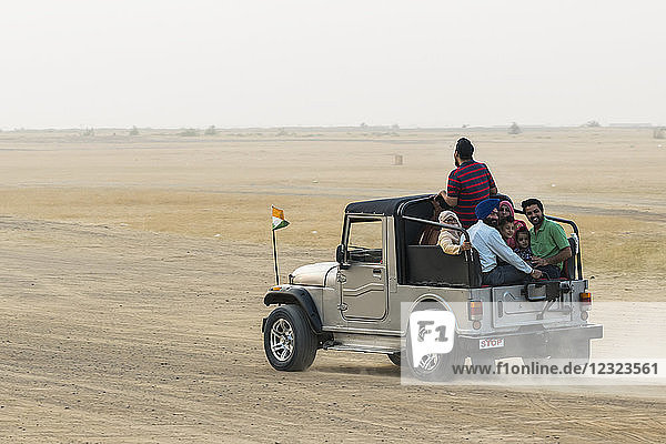 A family rides in the back of a recreational vehicle exploring the Sam sand dunes; Damodara  Rajasthan  India