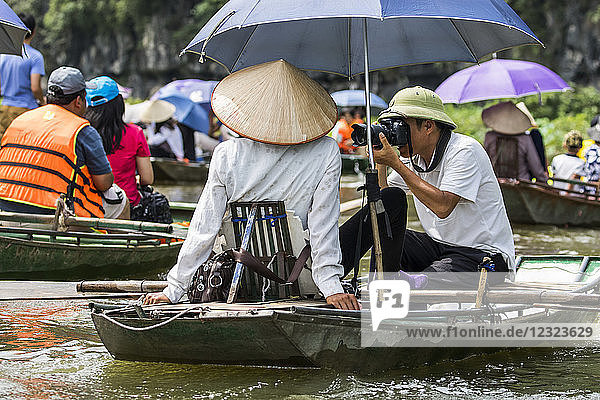 Photographer in a boat on the Ngo Dong River; Tam Coc  Ninh Binh  Vietnam
