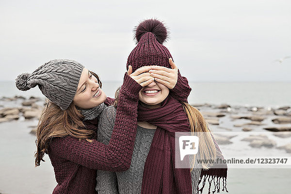 Two friends playing on the beach wearing knit hats and scarves  Woodbine Beach; Toronto  Ontario  Canada