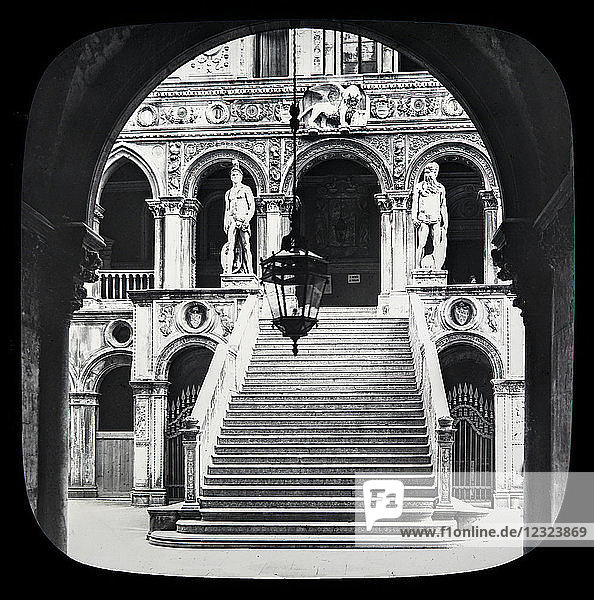 Magic lantern slide circa 1900.Victorian/Edwardian.Social History. The Beauties of Venice photographs created in 1888 Joseph John William ACWORTH F.I.C.  F.C.S.J. The Beauties of Venice. Scala dei Giganti  or Giant's staircase. This is a noble marble staircase leading to the Palace of the Doges  deriving its name from the colossal statues of Mars and Neptune at the top. It was on the top of these steps  and between those statues  that the doges used to be crowned in the olden times; and then  having heard mass in the cathedral close by  and made the tour of the Piazza  the new Doge retired to his future abode within. It was at the top of these steps  also  that the aged Doge Foscari fainted with anguish when forced to abandon a palace which for more than thirty years had been his home [B]