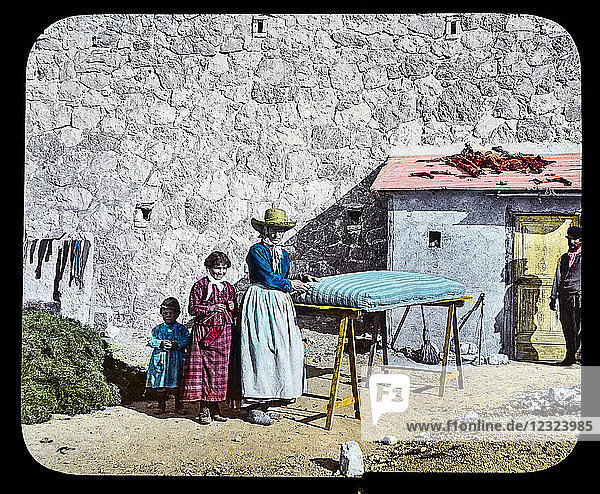 Magic Lantern slide circa 1900. Victorian or Edwardian era. The origional monchrome ( black and white ) photograph hand coloured.The photograph is the work of G.W. Wilson photographer and slide manufacturer 1823-1893.George Washington Wilson (7 February 1823 – 9 March 1893) was a pioneering Scottish photographer. The French Riviera and Monte Carlo (lecture ) Slide 46 Mattress cleaning Monaco. Lady  children and man cleaning a mattress outside their home.