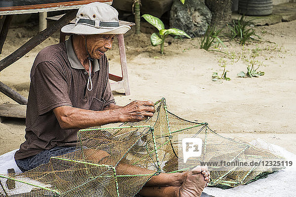 Fisherman sitting and repairing a net; Hoi An Ancient Town  Quang Nam  Vietnam