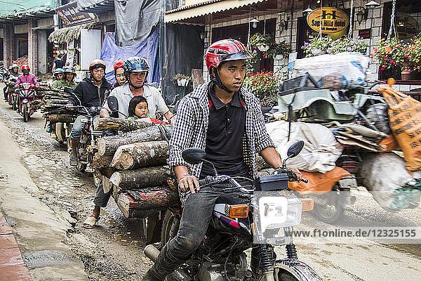 People hauling logs on motorbikes; Sapa  Lao Cai  Vietnam