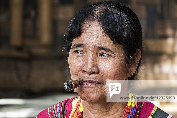 Lavae woman smoking a cigar in the ethnic village at Pha Suam  Bolaven Plateau; Champasak  Laos