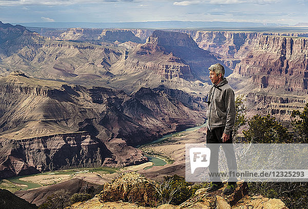 A senior man hiking in the Grand Canyon and standing on a ridge looking out over the landscape; Arizona  United States of America