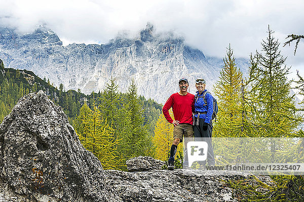 Male and female hikers standing on rock with autumn coloured trees and cloud-covered mountain range in the background; Sesto  Bolzano  Italy