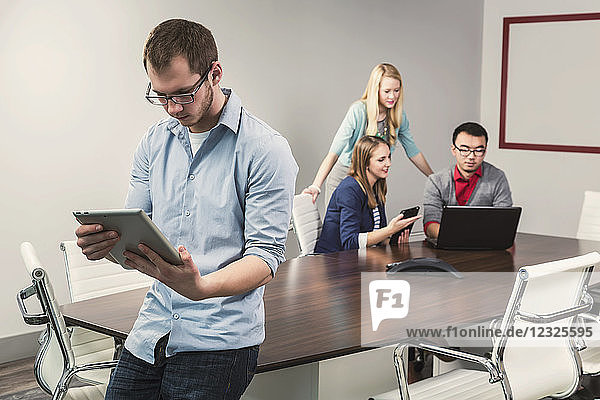 Young millennial business professionals working together in a conference room in a high tech modern business; Sherwood Park  Alberta  Canada