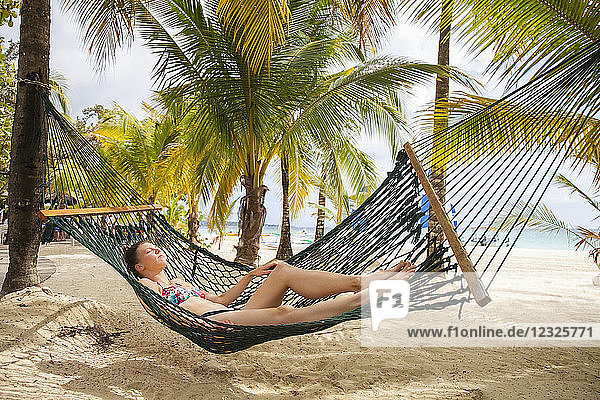 A young woman in a bikini lays in a hammock on a tropical beach with the ocean in the background; Negril  Jamaica
