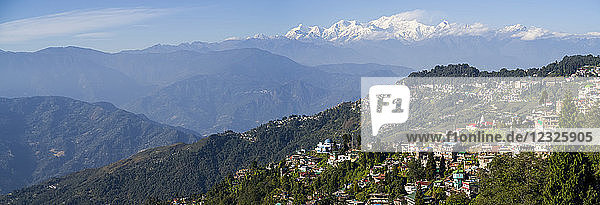 Town on a mountainside with the rugged  snow-capped peaks of the Himalayas in the distance; Darjeeling  West Bengal  India