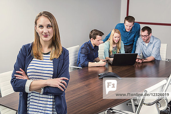 Young millennial businesswoman posing for the camera in a conference room of young professionals working together in a modern place of business; Sherwood Park  Alberta  Canada