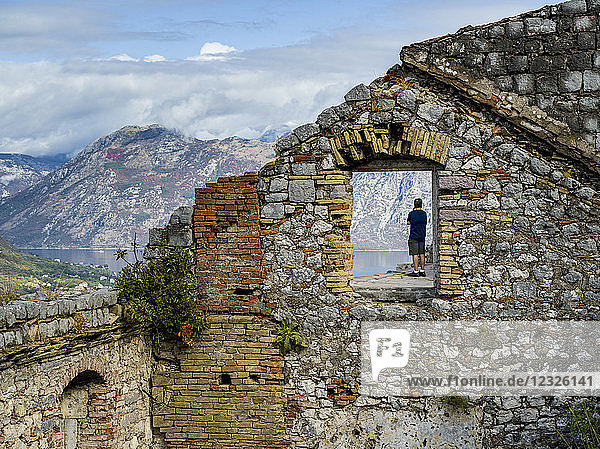 A male tourist standing at Kotor's Castle of San Giovanni looking out to the water below; Kotor  Montenegro