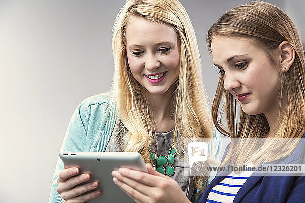 Two beautiful young women that are millennial business professionals working together and looking at a tablet at their workplace; Sherwood Park  Alberta  Canada